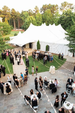 wedding-reception-cocktail-hour-on-grounds-of-hotel-with-tented-reception-area-in-background-lights