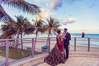 south-indian-couple-bride-in-red-wedding-gown-bride-in-formal-sari-groom-in-black-tuxedo-by-beach