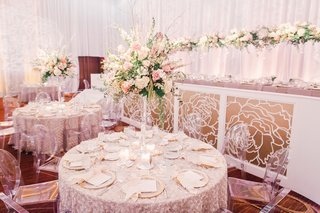 tall-wedding-centerpiece-on-texture-linen-round-table-with-white-pink-green-flowers-ballroom