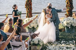 bride-and-groom-kissing-amid-cannon-confetti