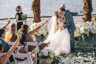 bride-and-groom-kissing-amid-cannon-confetti