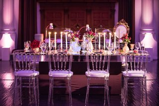 rectangular-wedding-mirror-table-with-clear-chairs-red-flower-arrangements-and-taper-candles
