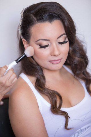 bride-getting-makeup-done-at-wedding-natural-curled-hair-headpiece-makeup-brush
