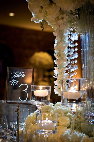 clear-lucite-table-number-sign-with-modern-calligraphy-table-number-next-to-white-centerpiece