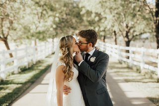 groom-holds-bride-by-the-chin-and-around-her-waist-while-kissing-her-as-they-stand-on-a-path