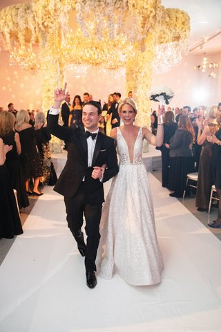bride in berta wedding dress plunging neckline and groom in tux hands up after jewish ceremony