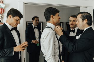 best-man-adjusting-the-grooms-bow-tie-groomsmen-getting-ready-pictures