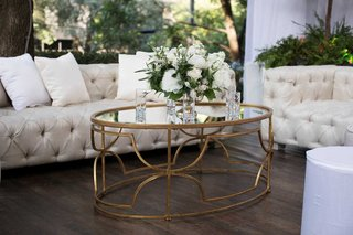 wedding-cocktail-table-gold-ivory-chesterfield-sofa-tufted-greenery-white-flowers-pillows