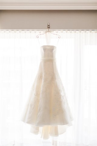 vera wang wedding dress hanging up in front of window bridal stylist dear maradee wahl
