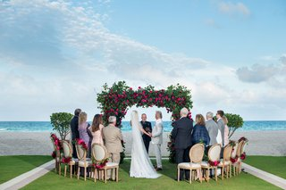 wedding-ceremony-beach-grass-lawn-overlooking-ocean-greenery-arch-pink-rose-flowers-wood-chair-small