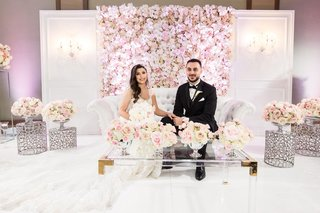 wedding photo of bride and groom on sweetheart table stage tufted settee flowers pink pastel