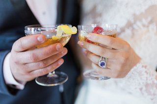 coupe-champagne-glasses-filled-with-drinks-with-lemon-and-raspberry-garnish-amethyst-engagement-ring