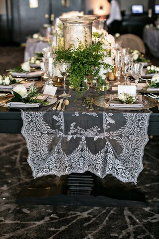 wedding reception ballroom wood table with lace sheer runner fresh greenery etched candle holders