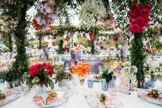 wedding reception long white table orange flower print china pink orange flowers greenery