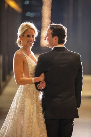 bride in berta wedding dress illusion gown with deep plunging neckline and groom lighting