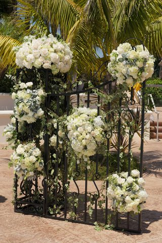 wrought-iron-gate-with-white-flowers-and-greenery