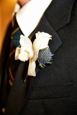 grooms-boutonniere-of-white-orchid-rose-and-blue-flower-on-charcoal-blazer-lapel-tartan-tie