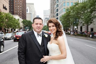 bride-and-groom-embrace-in-chicago-on-a-busy-street