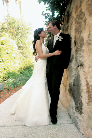 bride-in-a-vera-wang-gown-and-groom-in-a-black-tuxedo-with-an-orchid-boutonniere