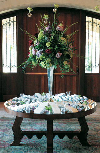 mirror-top-place-card-table-with-a-large-bouquet-of-red-green-and-lavender-flowers