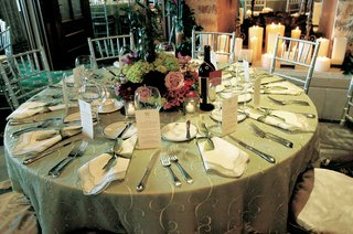 wedding-reception-table-with-green-tablecloth-and-red-green-and-lavender-flowers