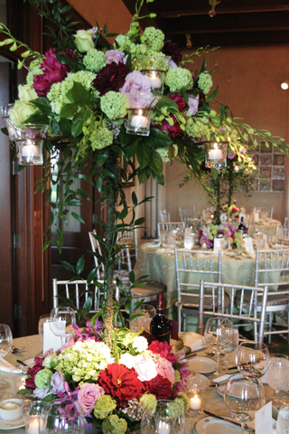 tall-flower-centerpiece-with-green-red-and-lavender-flowers-at-its-base-and-on-top