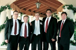 groom-in-black-tuxedo-and-tie-and-groomsmen-in-black-tuxedos-and-red-ties