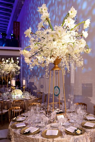 wedding-reception-centerpiece-of-white-flowers-in-a-gold-urn-sitting-on-art-decor-risers