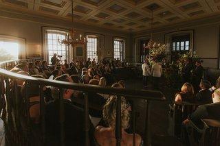 wedding-ceremony-colony-house-newport-rhode-island-sunlight-dark-chandelier-moody-flowers
