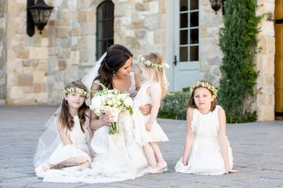bride-in-monique-lhuillier-wedding-dress-holding-bouquet-with-three-flower-girls-in-flower-crowns