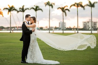wedding-portrait-bride-and-groom-in-palm-beach-palm-trees-sunset-lace-trim-cape-instead-of-veil