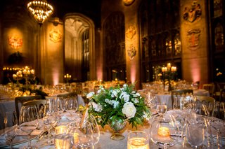 wedding-centerpiece-white-roses-ferns-and-other-greenery-warm-yellow-lighting
