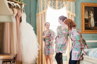 bridesmaids-in-colorful-robes-get-excited-while-looking-at-wedding-dresses-before-ceremony