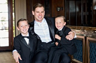groom-with-arm-around-ring-bearers-ring-bearer-sitting-on-grooms-lap