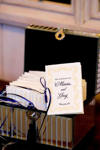 wedding-ceremony-program-tied-with-blue-ribbon-yellow-design-in-mirror-box