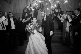 black-and-white-photo-of-bride-and-groom-smiling-during-sparkler-exit-at-wedding-reception