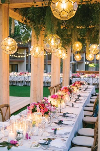 wood-structure-with-lantern-pendants-greenery-string-lights-pink-flowers-candlelight-long-table