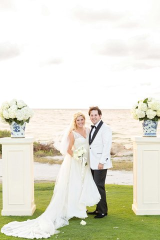 bride-and-groom-in-white-at-ocean-lawn-destination-wedding-ceremony-white-risers-hydrangea-flowers