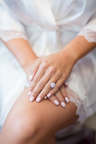 large-diamond-engagement-with-halo-and-thin-band-with-pale-pink-manicure-nails