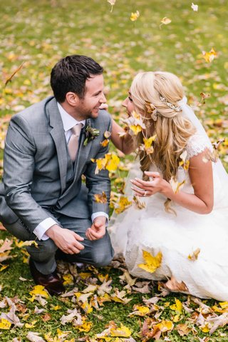 bride-and-groom-knell-in-fall-leaves-and-throw-leaves-in-the-air