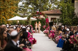 bridesmaids-walking-down-white-aisle-runner-pink-roses-in-urns-archway-at-entry-greenery-pink-flower