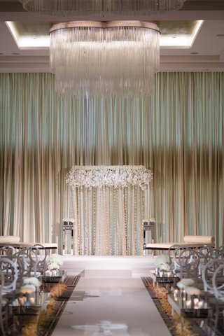 wedding-ceremony-chicago-ballroom-chandelier-white-flower-round-back-chair-and-flower-petals-aisle