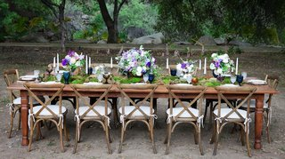 outdoor-wedding-reception-with-wood-table-chairs-moss-runner-pink-purple-white-flowers