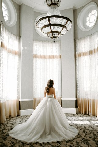 bride-in-tara-keely-wedding-dress-ball-gown-in-room-with-tall-windows-chandelier-sunny-sunlit