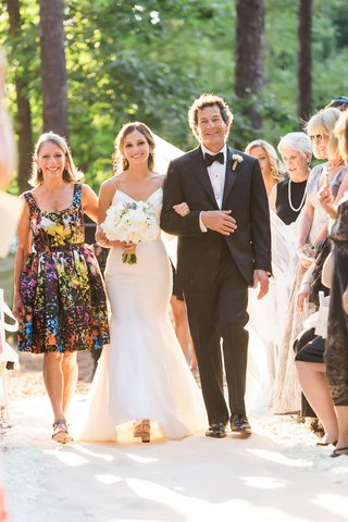bride-walking-down-aisle-with-father-in-tuxedo-and-mother-in-short-cocktail-dress-colorful-design