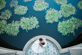 birds-eye-view-of-bride-and-groom-kissing-next-to-pond-with-greenery-skirball-cultural-center
