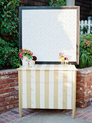 gold-and-white-stripe-dresser-with-frame-of-escort-cards-pinned-to-board-with-gold-bow-pins