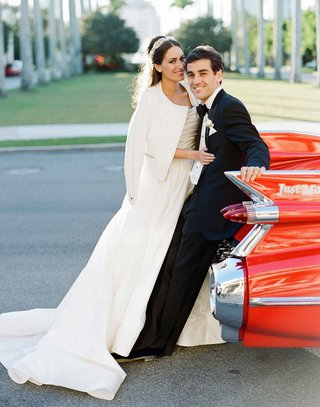 bride-in-cool-white-jacket-over-wedding-dress-with-groom-in-tuxedo-at-back-of-their-classic-red-car
