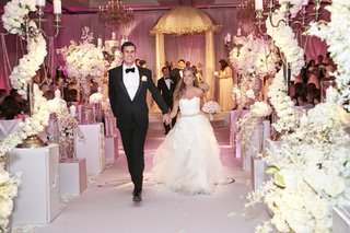 couple-walking-on-monogrammed-aisle-runner