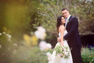 bride-in-monique-lhuillier-crop-top-wedding-dress-held-by-groom-in-armani
